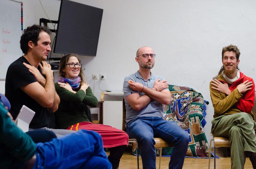 """Auenweide-Mitglieder sitzen im Sesselkreis. Hände sind überkreuzt vor der Brust um """"Konsens"""" zu signalisieren"""